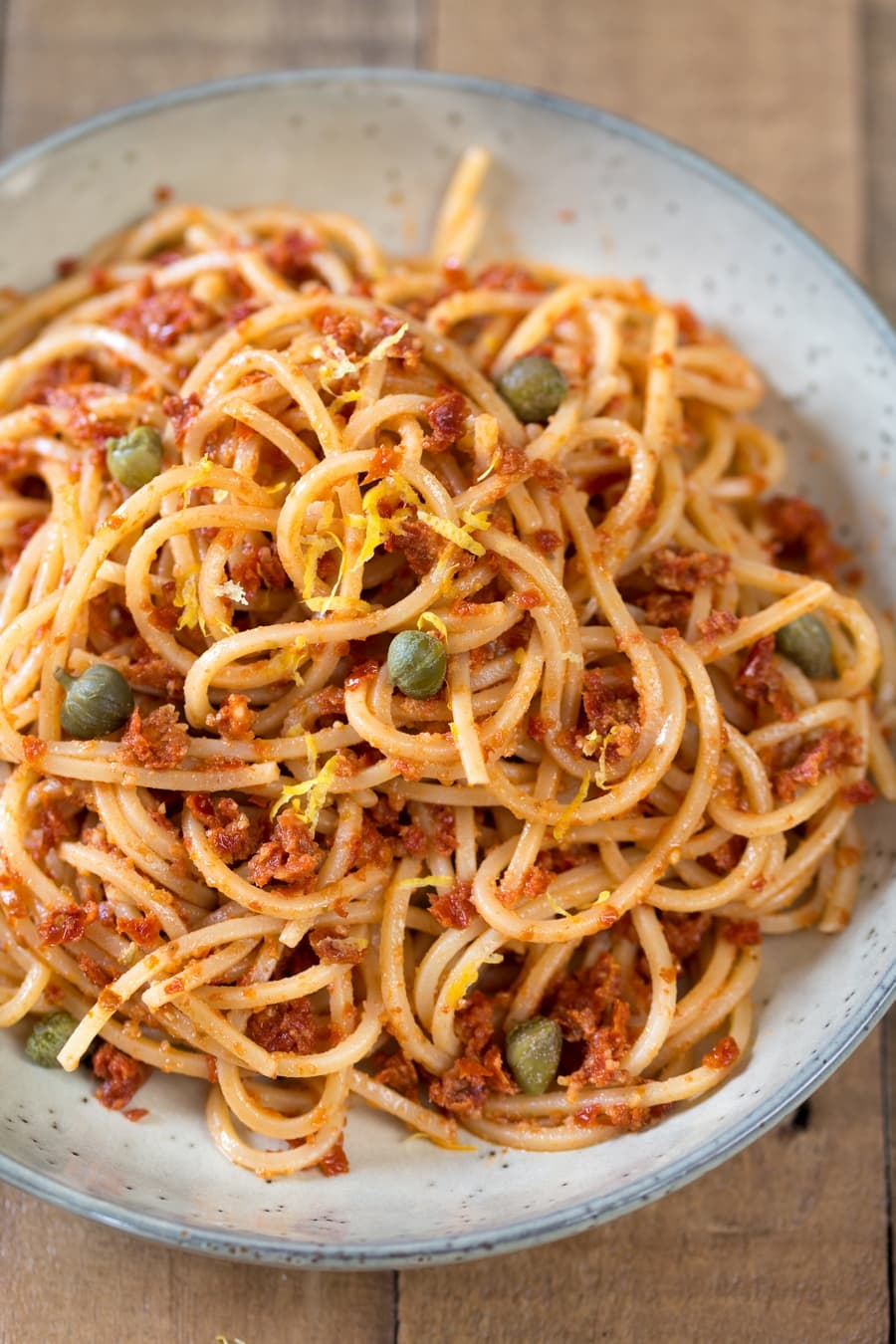 Spaghetti with sun-dried tomato pesto sauce with capers and lemon zest.