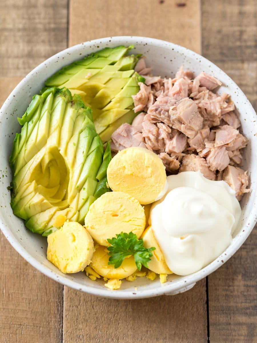 Avocado, egg yolks, tuna and mayonnaise in a bowl.