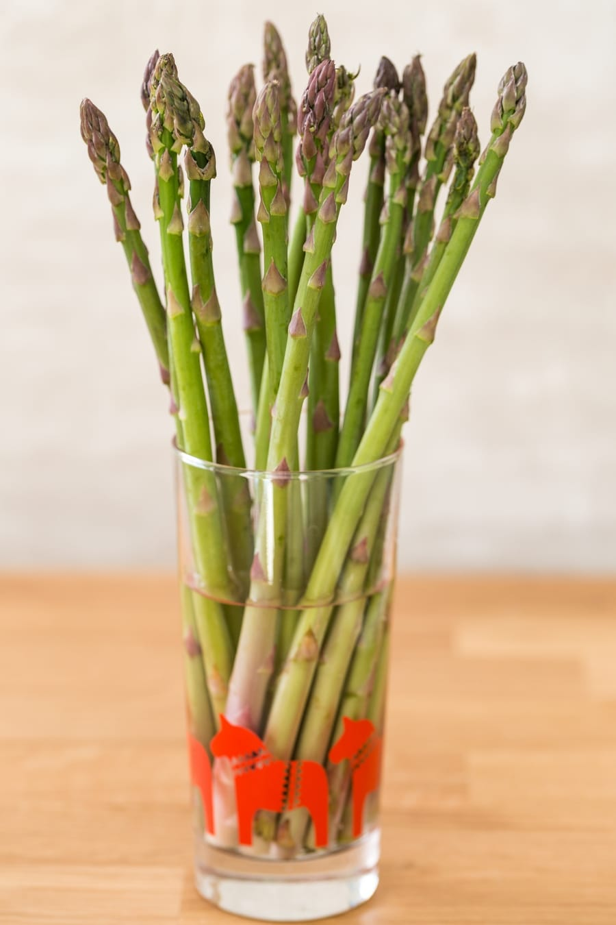 Bunch of green asparagus ina glass of water for longer keeping.