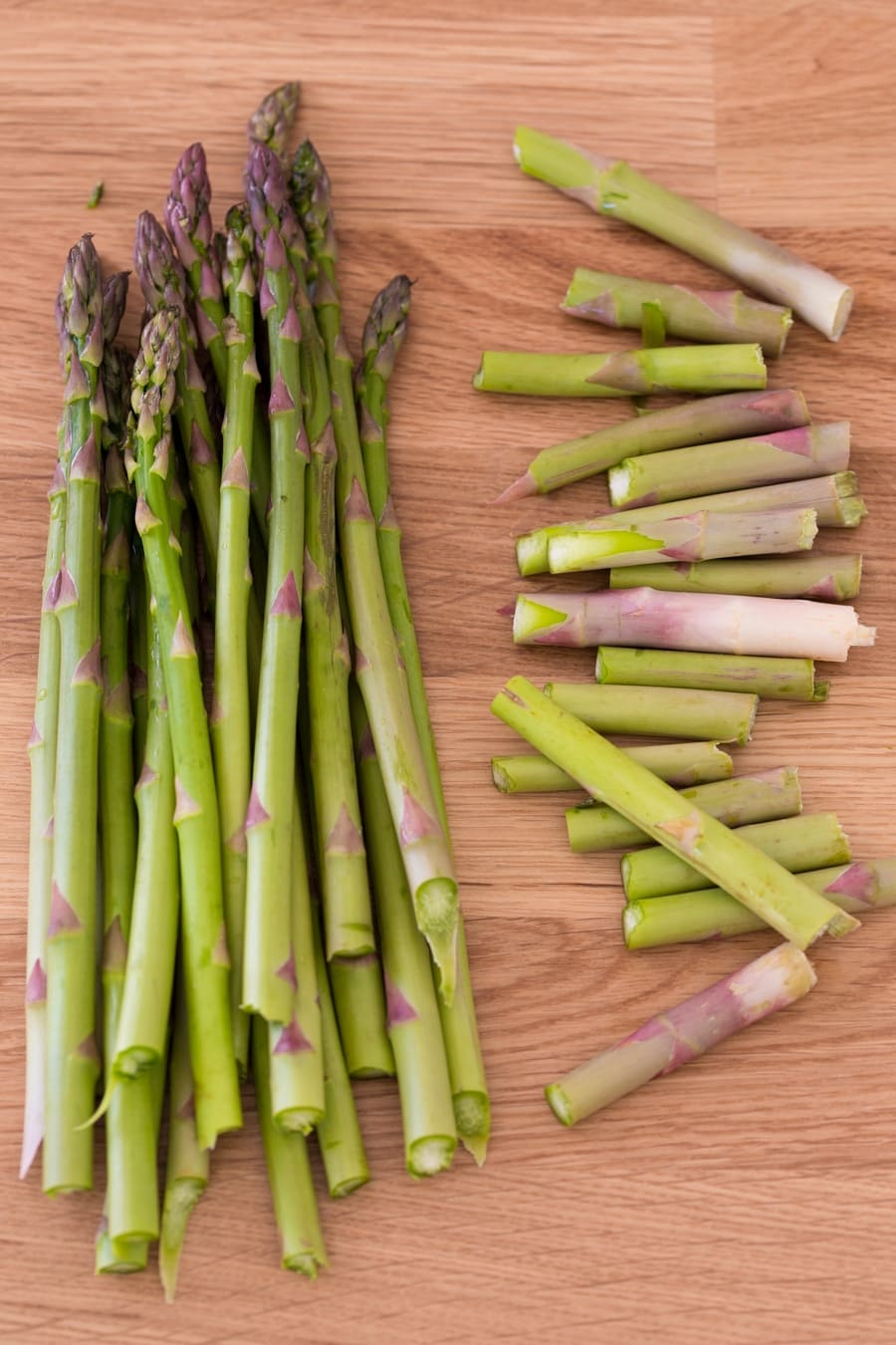 Asparagus stalks with woody ends separated.