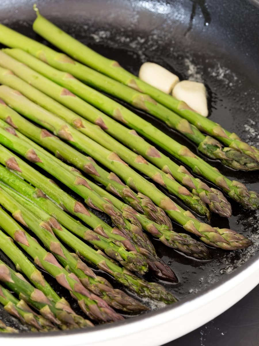 Green asparagus sautéed in cast iron skillet.