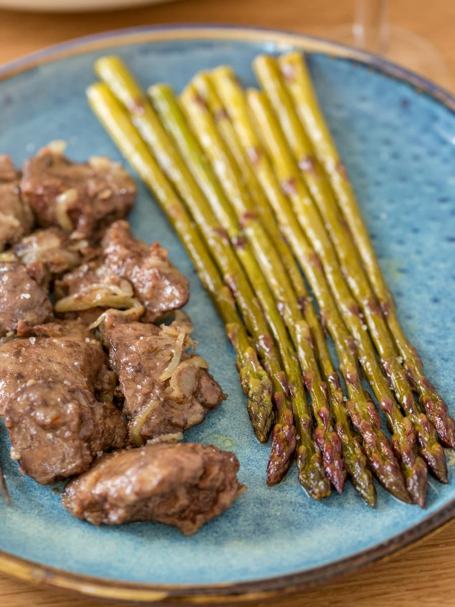 Sautéed white wine asparagus served as side dish to chicken livers with onion.