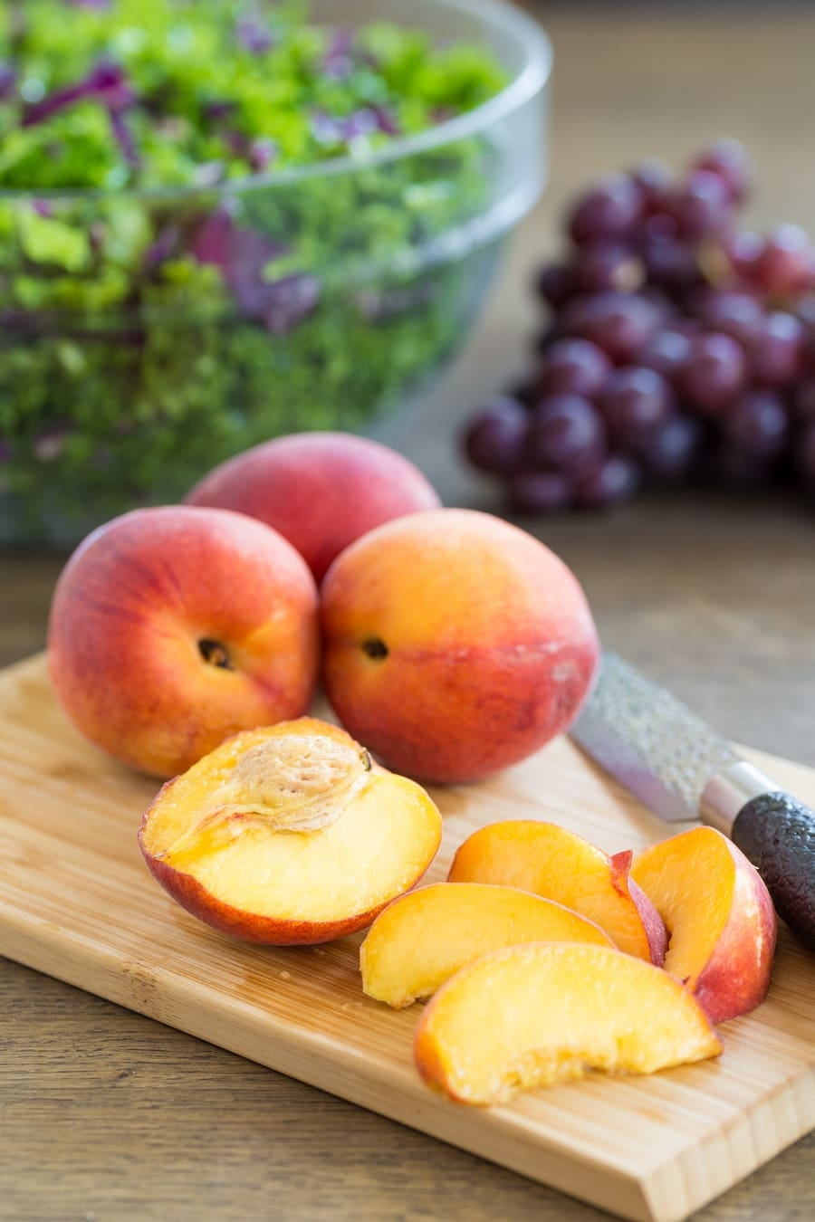 Fresh peaches on a cutting board.