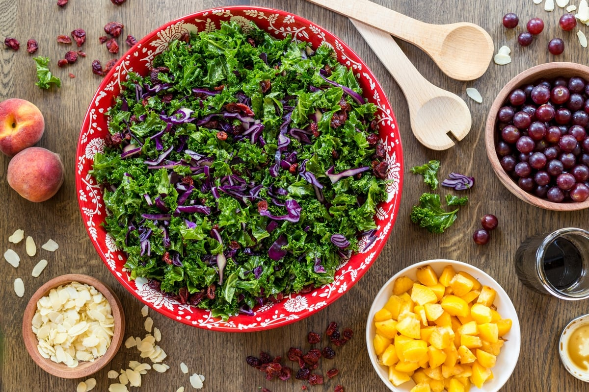 Flatlay view of kale salad in a red bowl. Small bowl with chopped fruits placed around it.