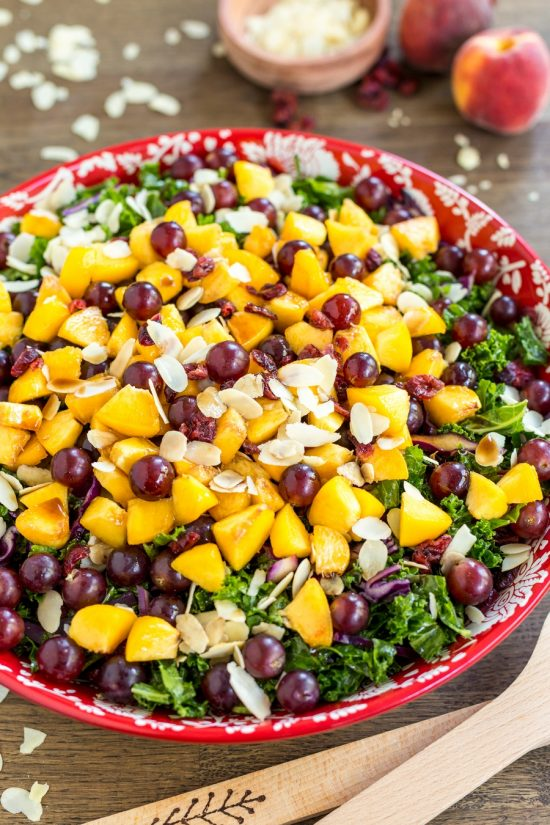 Fruity kale salad with peaches, grapes and almonds. With vegan balsamico dressing.
