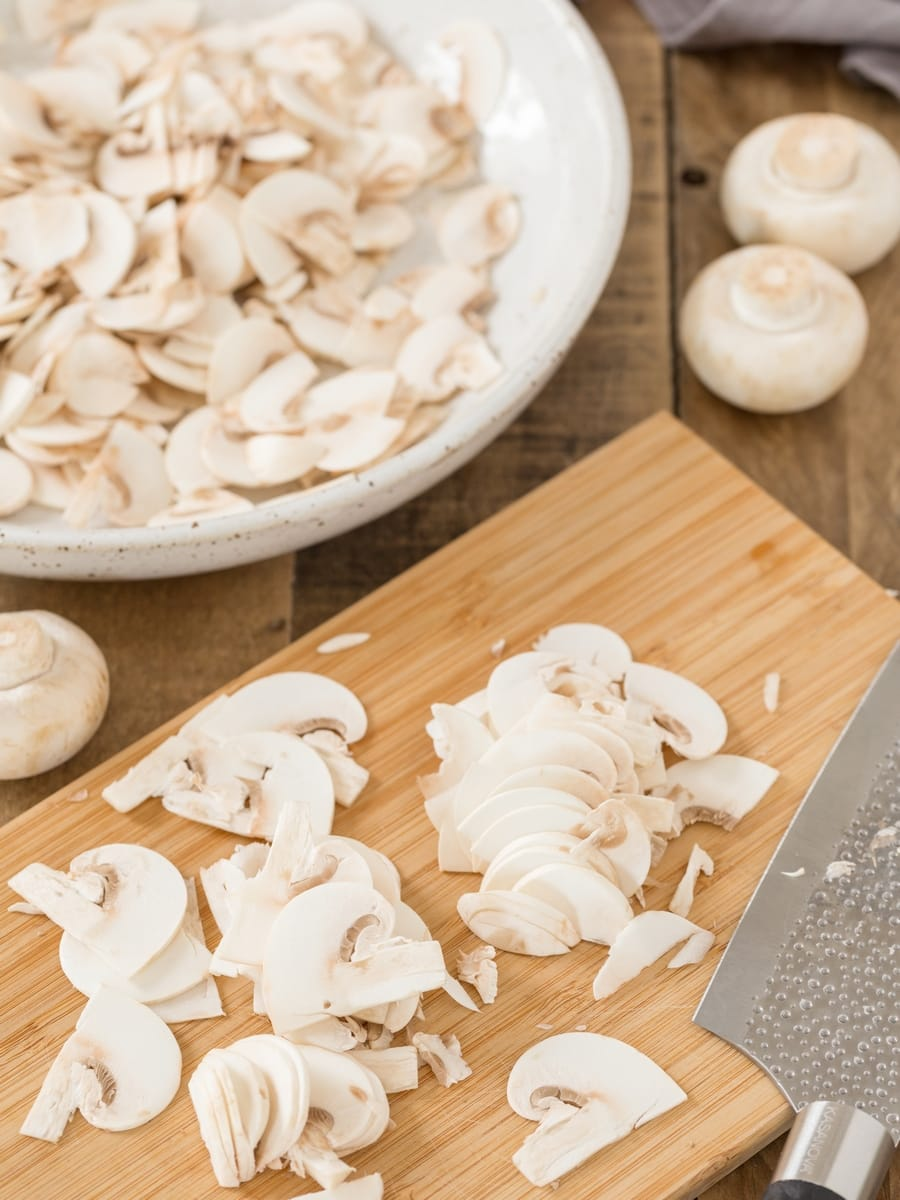 Cultivated mushrooms thinly sliced on a bamboo chopping board, sliced mushrooms in a bowl.