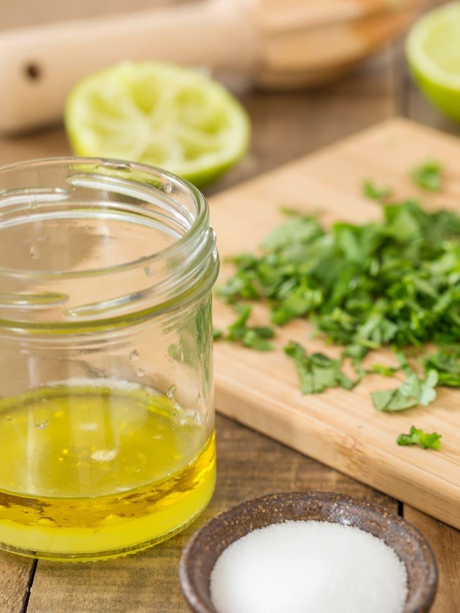 Succo di lime e olio d'oliva mescolati in un barattolo, coriandolo tritato e sale a parte.