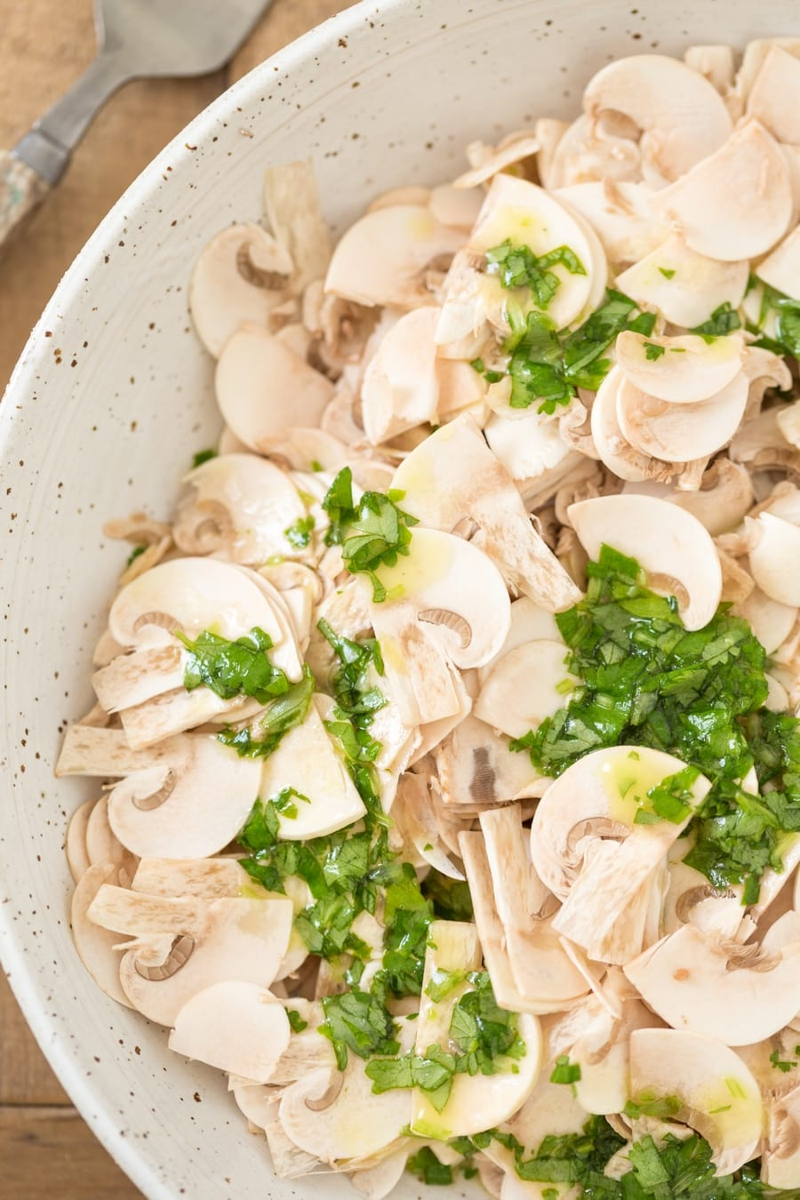 Cilantro lime dressing poured over thinly sliced mushrooms to make raw mushroom salad.