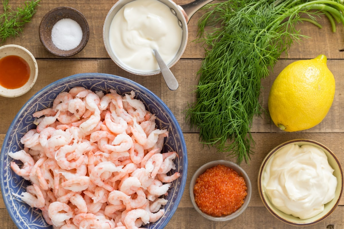 Ingredients needed to make Swedish shrimp salad: hand-peeled shrimps, mayo, sour cream, gill, lemon, fish roe and sriracha.