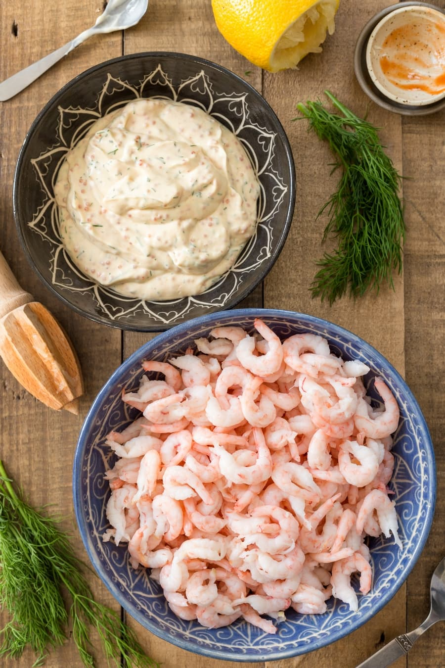 Bowl of creamy base for shrimp salad and bowl with shrimps.