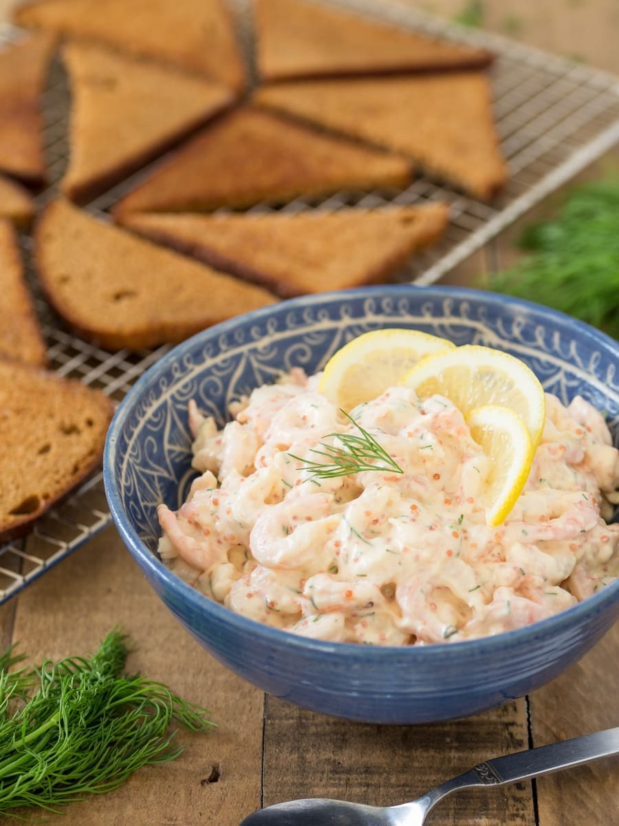Swedish shrimp salad skagenröra in a bowl, toasted rye bread in the background.