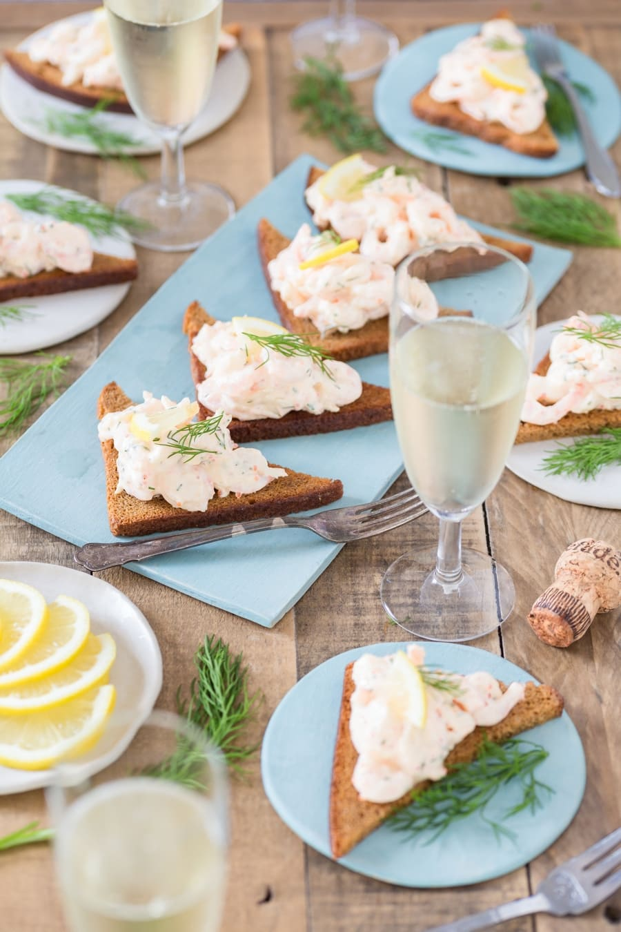 Skagenröra shrimp salad on rye toast, glasses of prosecco around.