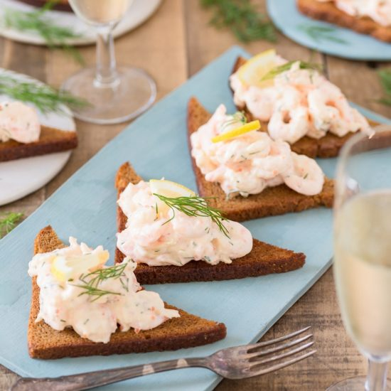 Rye toast with shrimp salad skagenröra on a blue plate.