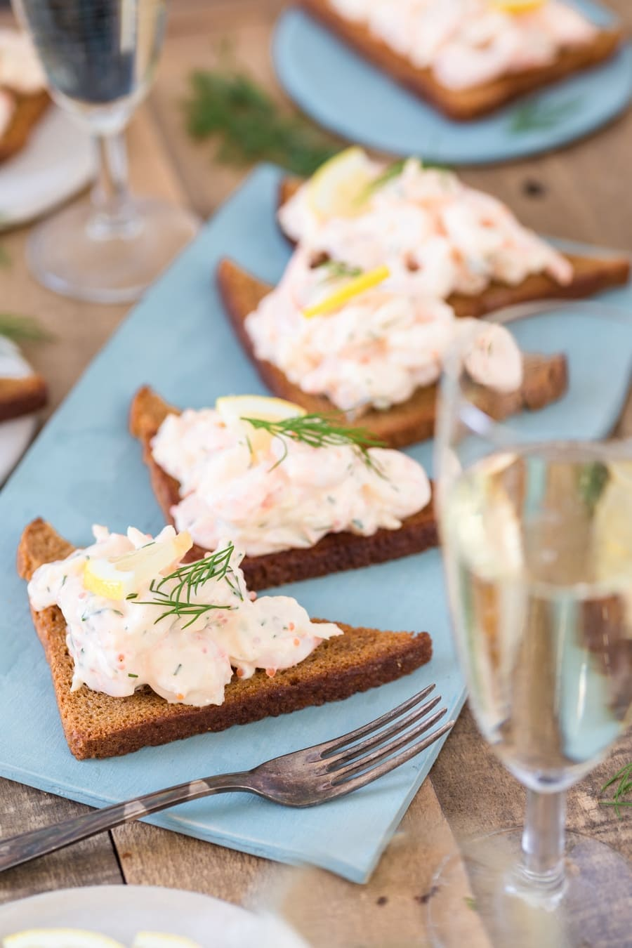 Swedish skagenröra shrimp salad on toasted rye bread, served with prosecco.
