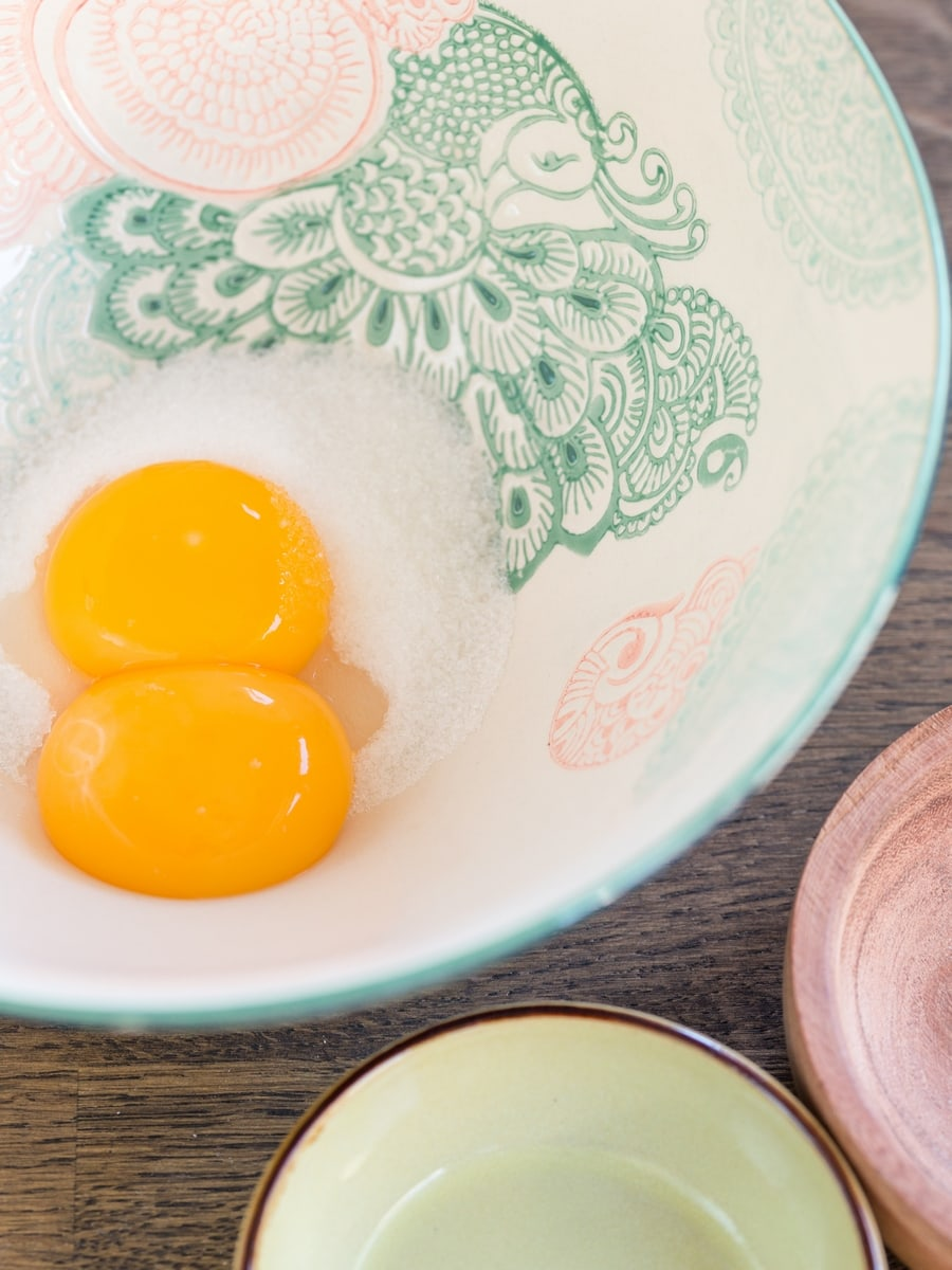 Two egg yolks in a bowl with granulated sugar.