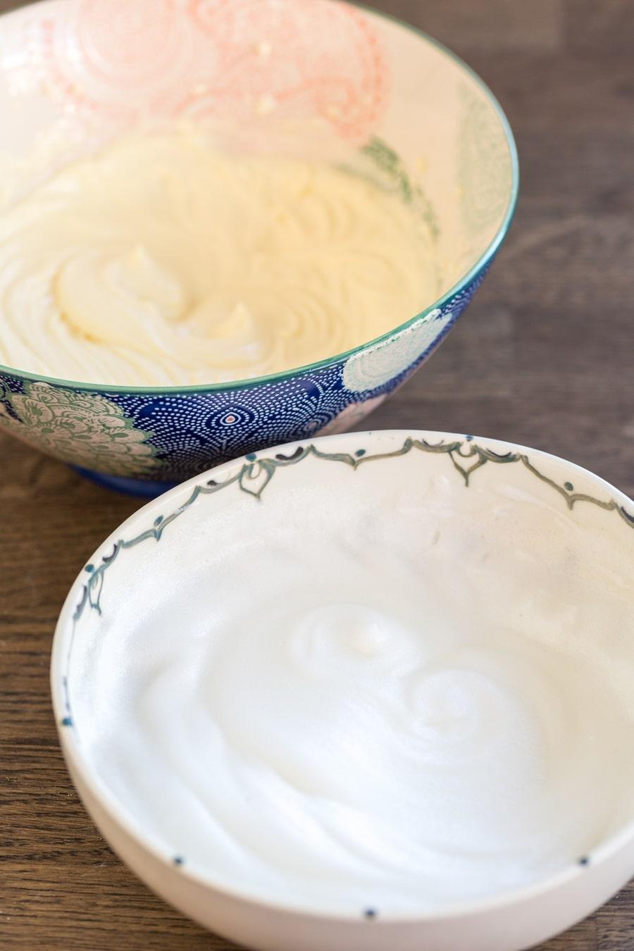 One bowl with beaten egg whites, one bowl with mascarpone and egg yolk cream.