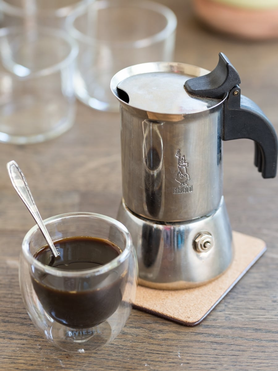Bialetti moka pot and small see-through cup of coffee.