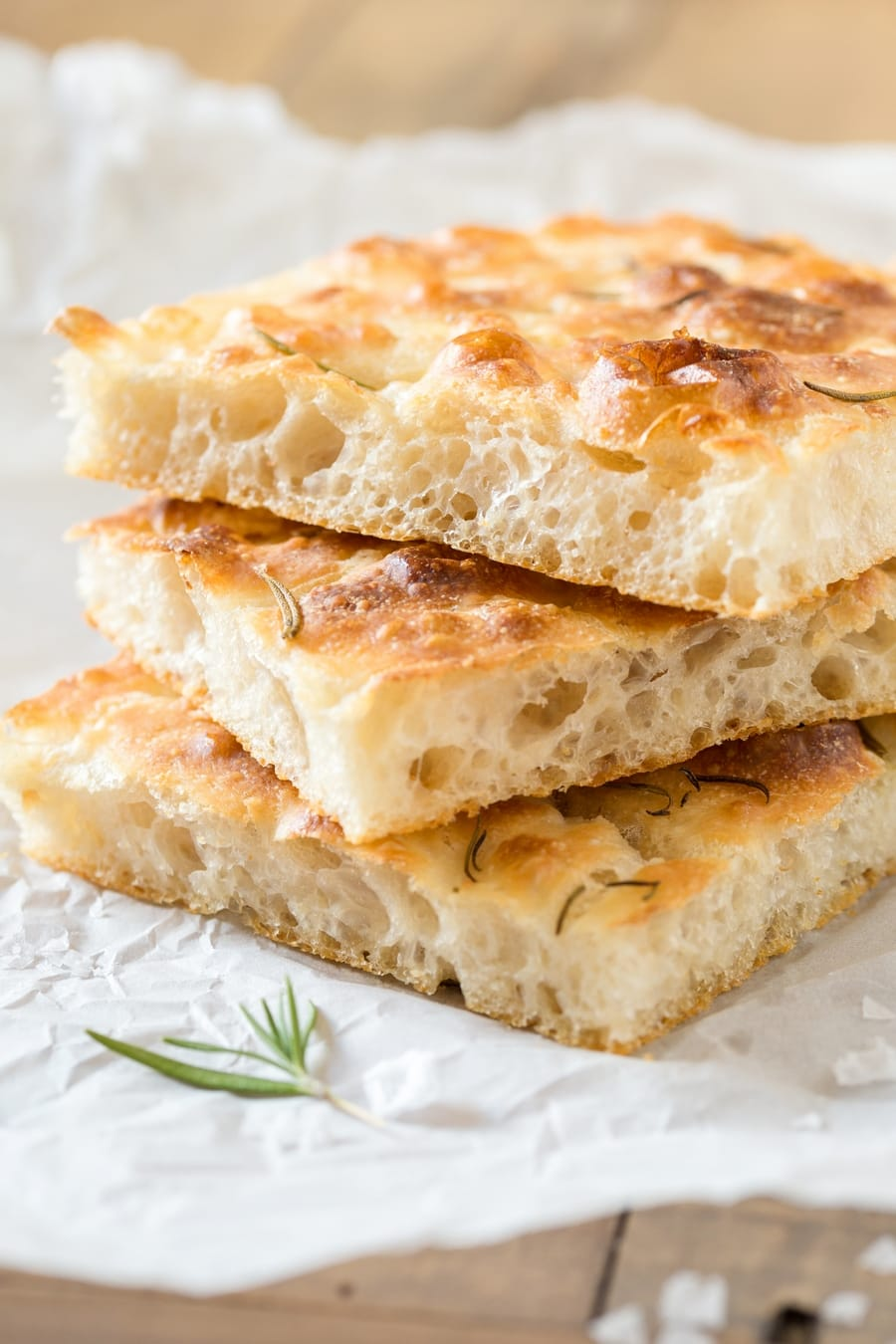 Slices of focaccia, stacked on white paper.