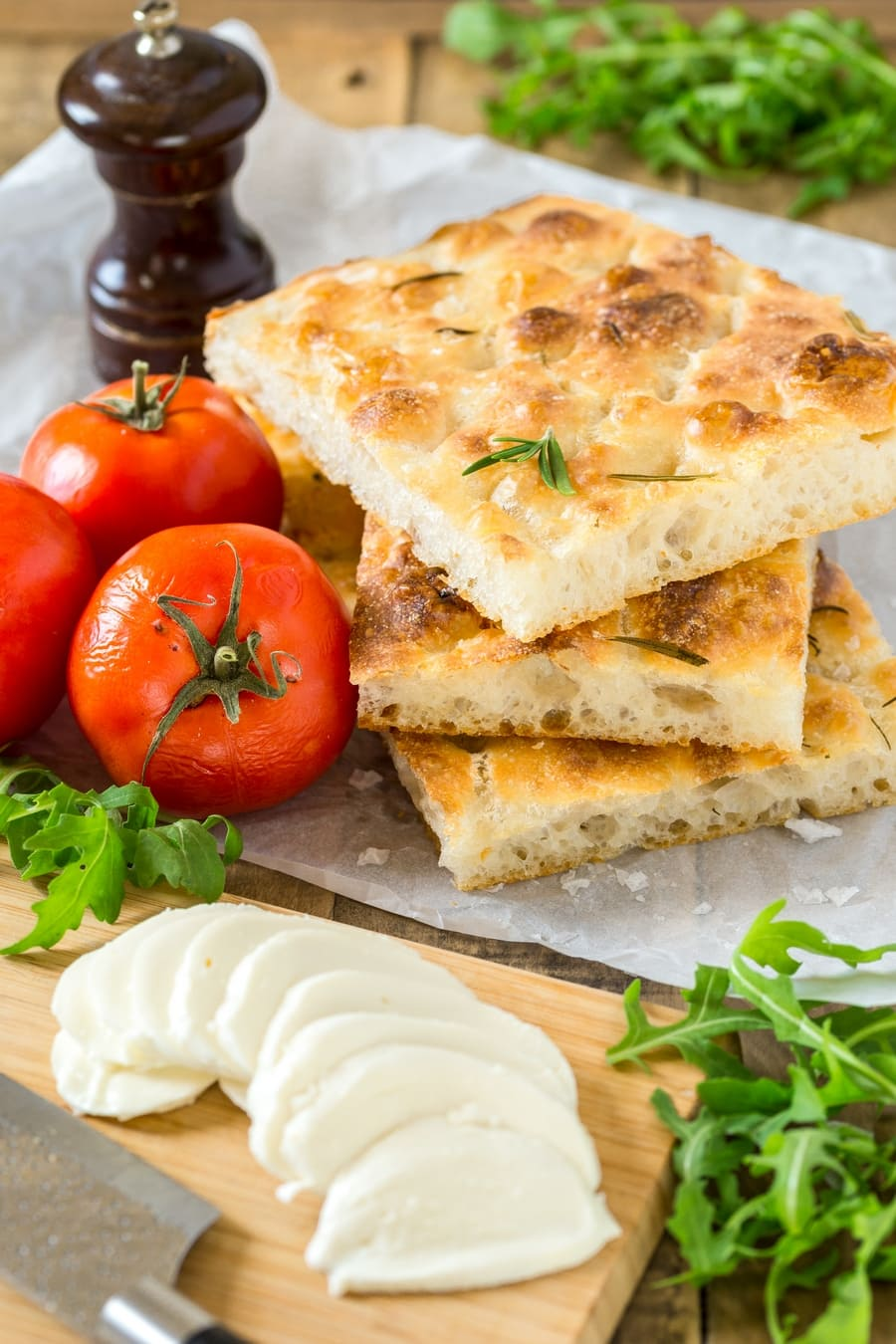 Fresh tomatoes, focaccia slices, sliced mozzarella, pepper and rucola: the ingredients to make caprese focaccia sandwich.