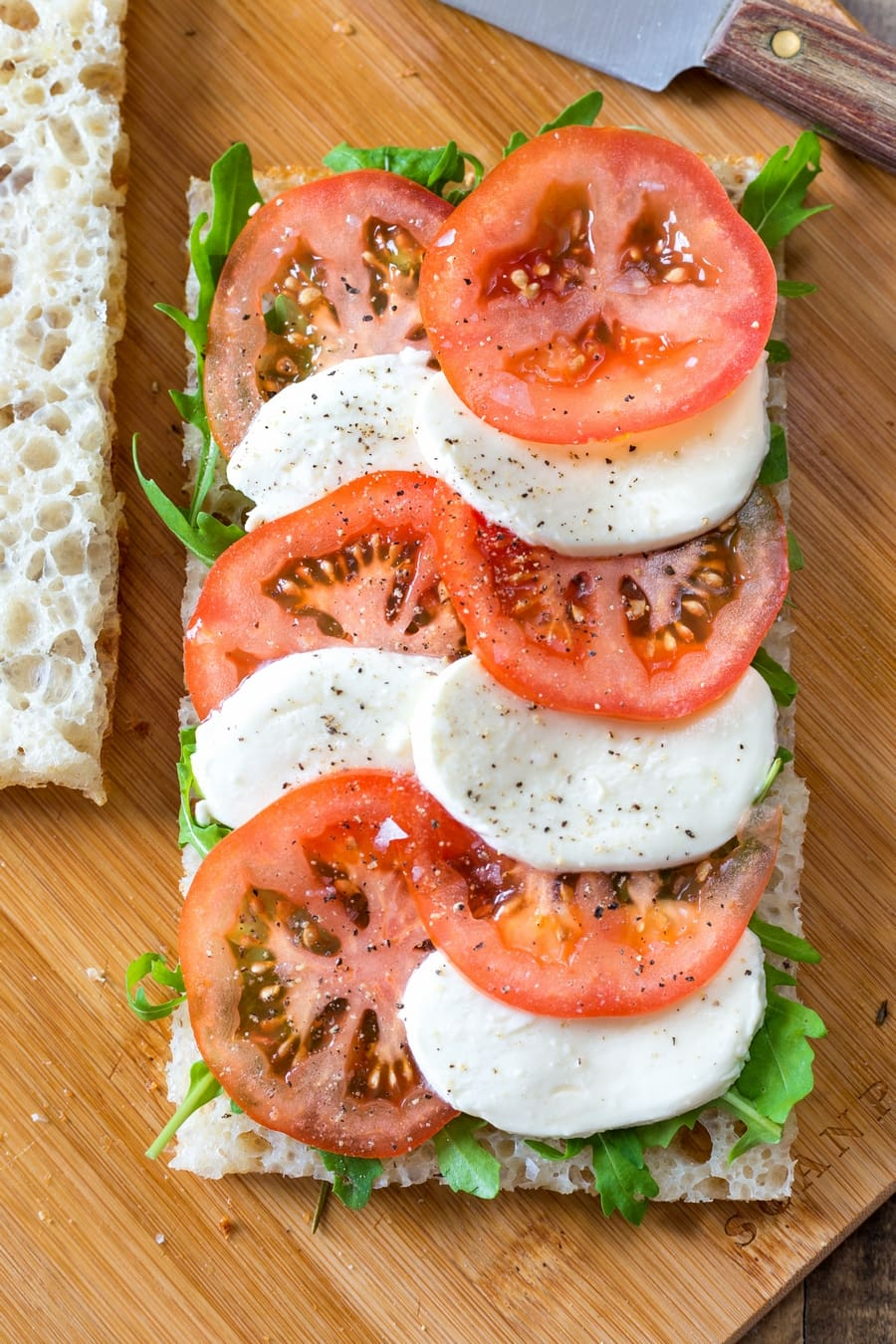 Caprese tomato and mozzarella slices on focaccia bread with rocket salad.