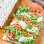 Tomato mozzarella sandwich on focaccia bread. Caprese sandwich with rocket leaves.