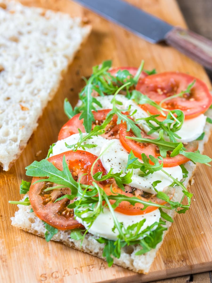 Tomato mozzarella sandwich on focaccia bread. Caprese sandwich with rocket leaves.