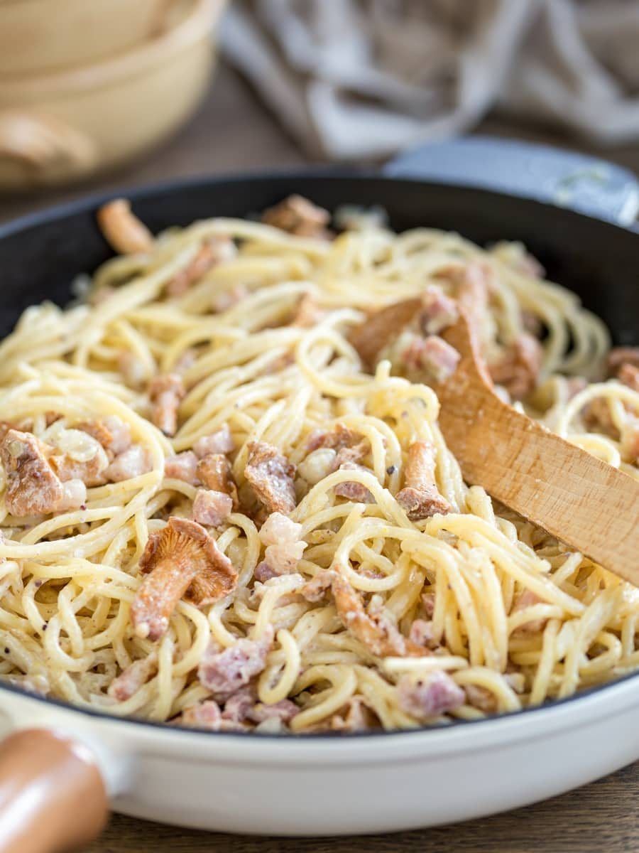 Creamy mustard pasta with bacon and mushrooms in a skillet.