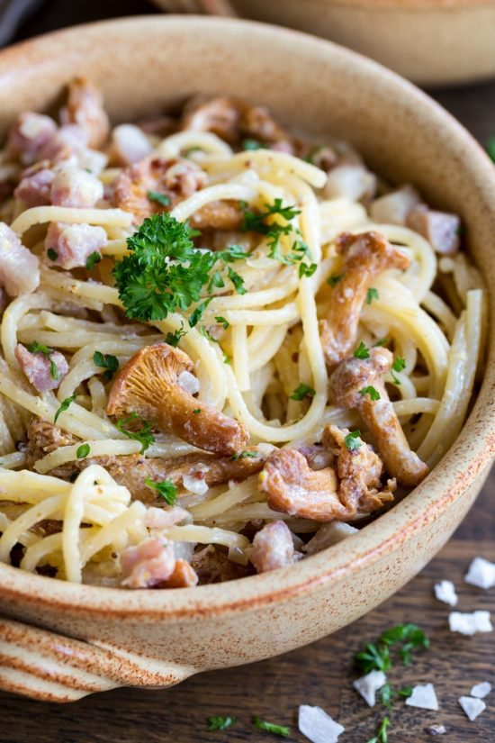 Closeup of creamy mustard pasta with bacon and chanterelles.