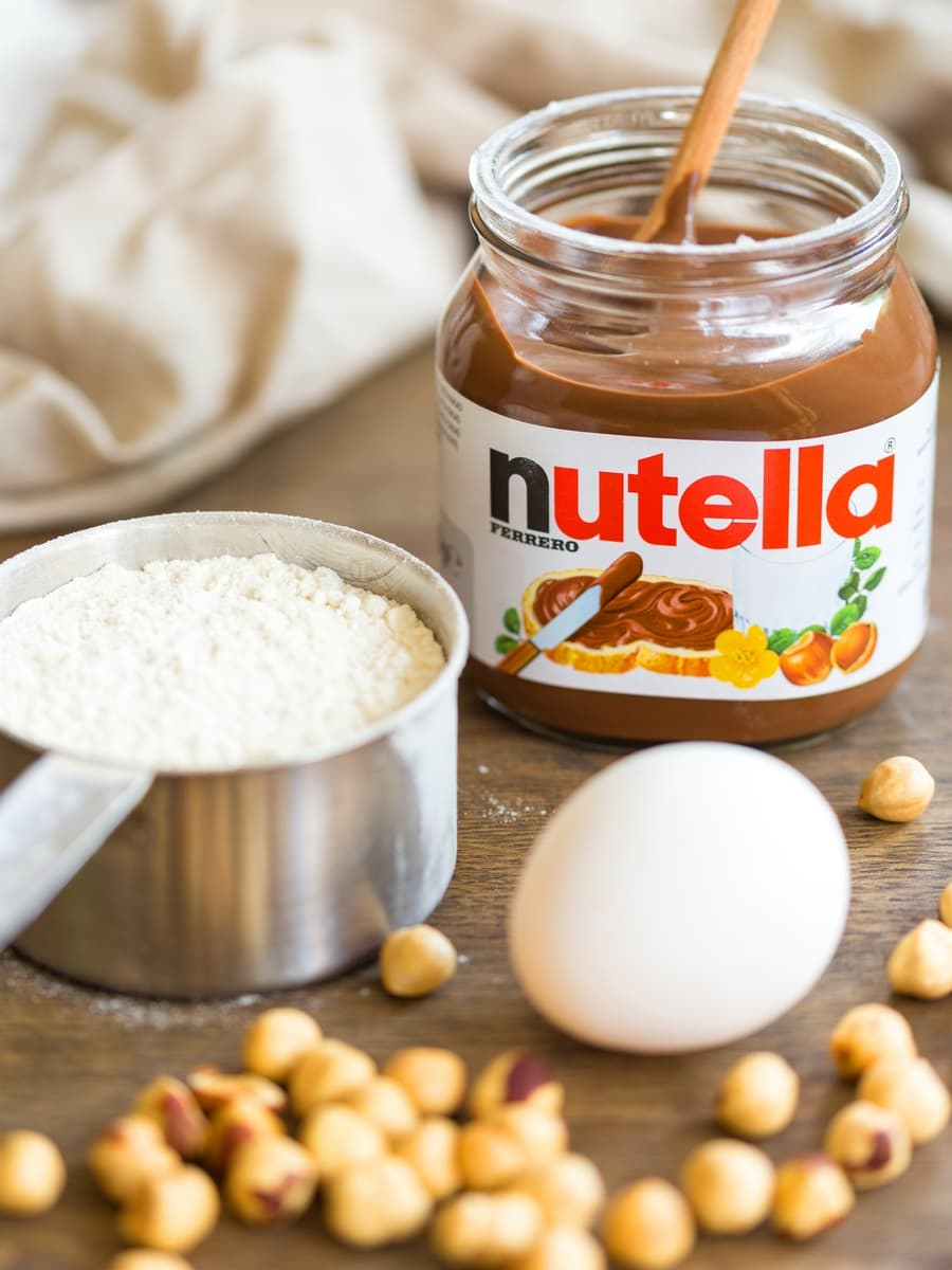 Nutellotti ingredients on a table: one egg, flour, Nutella and whole hazelnuts.