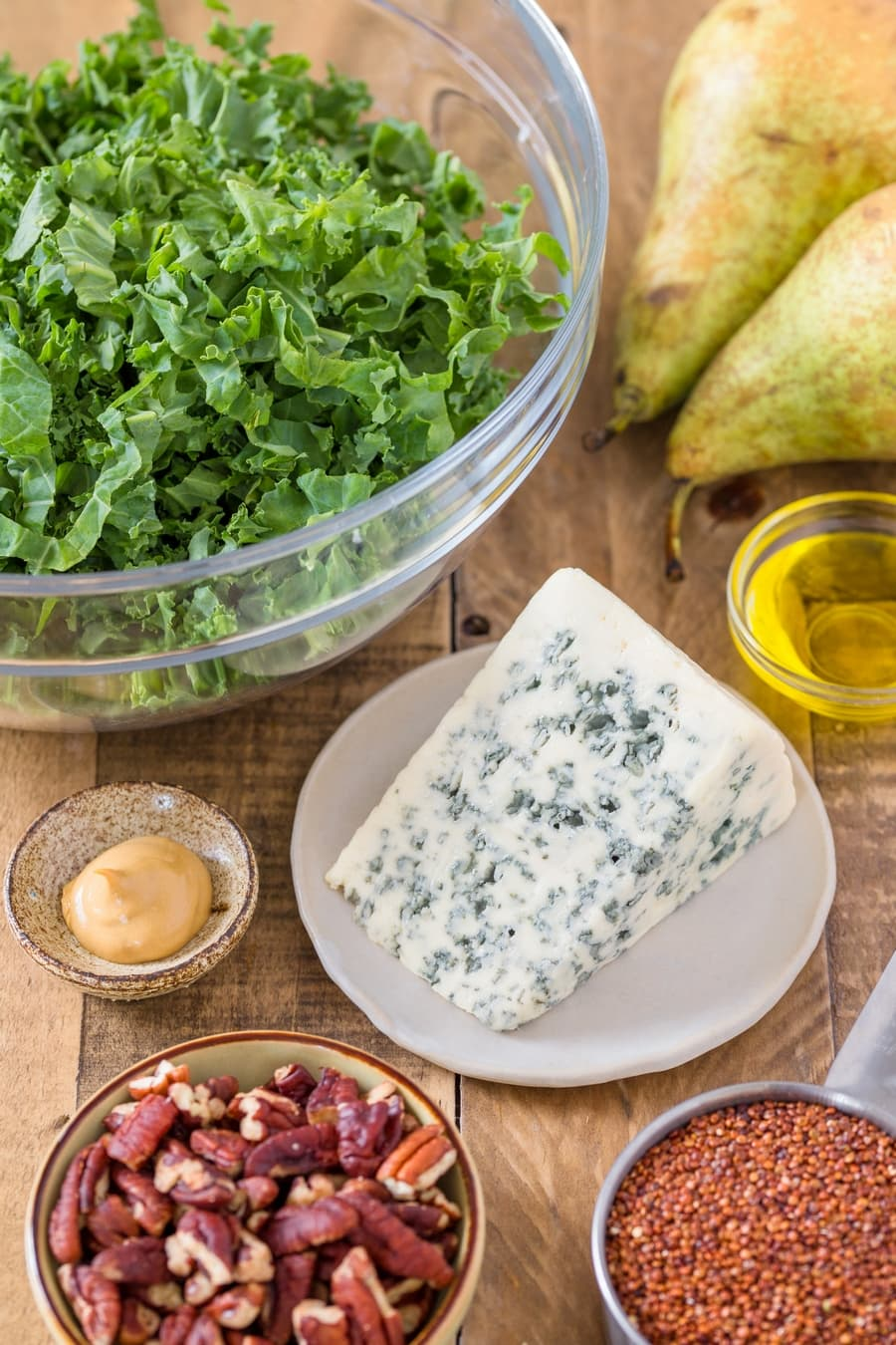 A block of blue cheese surronded by kale, pecans, pears, quinoa and condiments in bowls.
