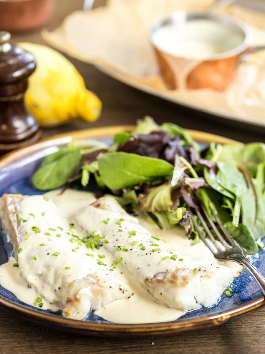 Baked lemon pepper cod with cream sauce served with a side of salad.
