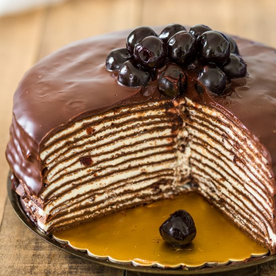 Black Forest crepe cake is the crepe cake version of the traditional German cake. Made with chocolate crepes and layers of whipped cream and minced sour cherries in syrup, it is then covered in chocolate ganache and decprated with more amarena cherries. Make Black forest cake on the stovetop swapping the sponge cake for crepes!