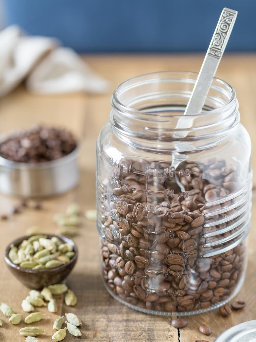 Mason jar withh coffee beans in, cardamom pods in a small bowl beside.