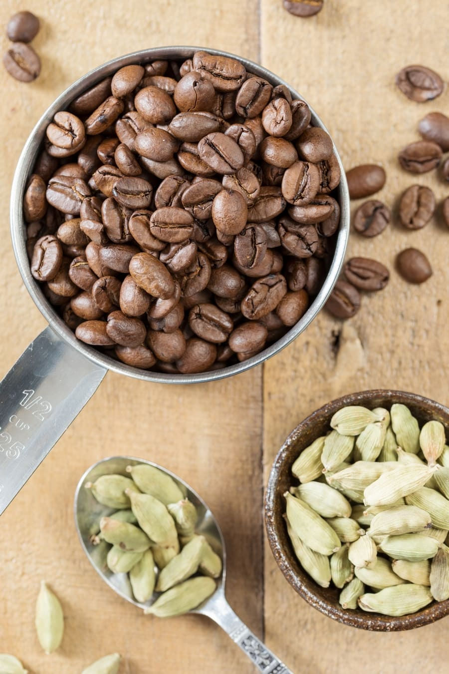 Overhead view of coffee beans and cardamom pods.