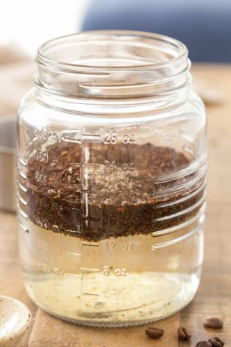 Ground coffee added to water in mason jar.