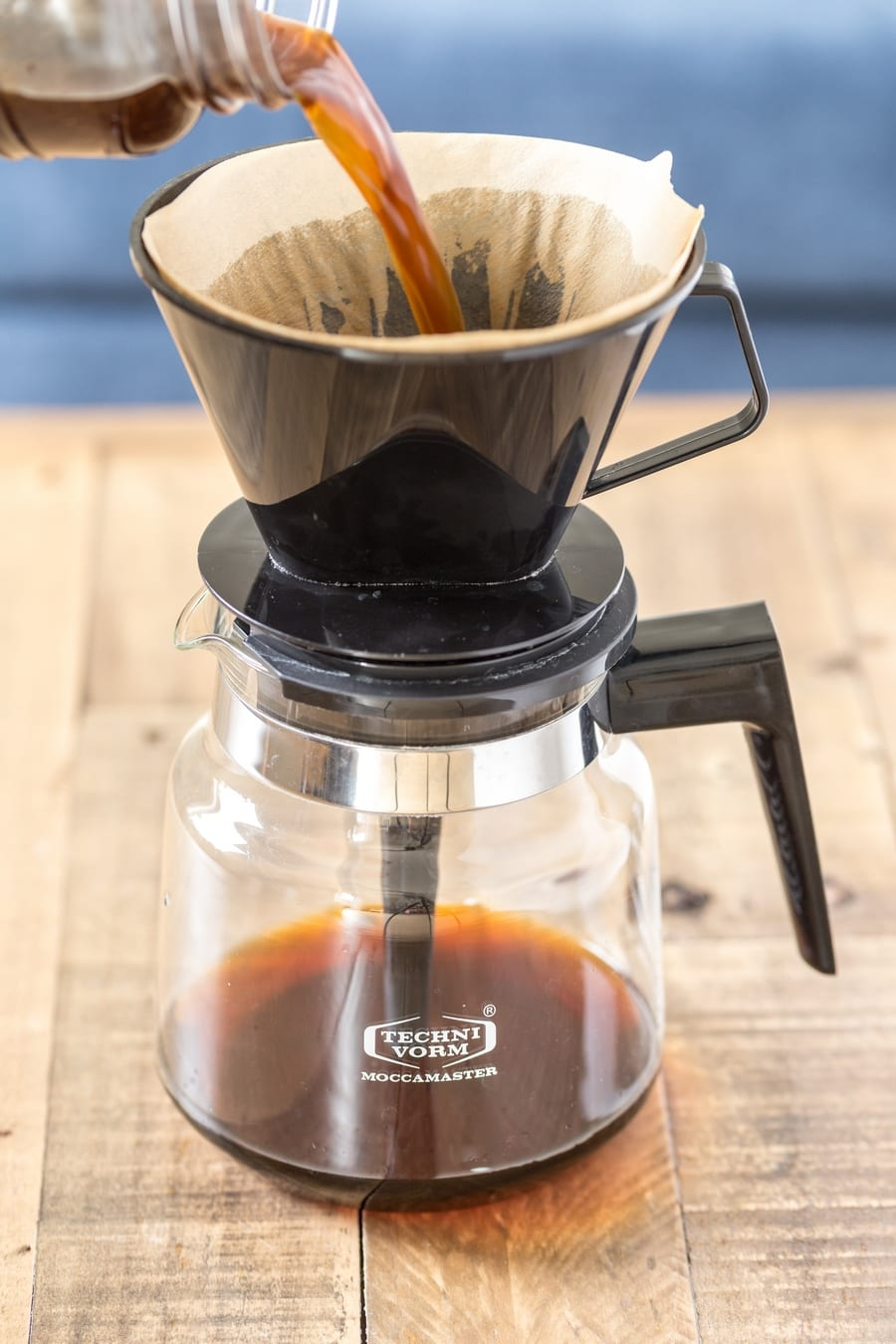 Cold brew coffee being filtered through a pour-over coffee maker.