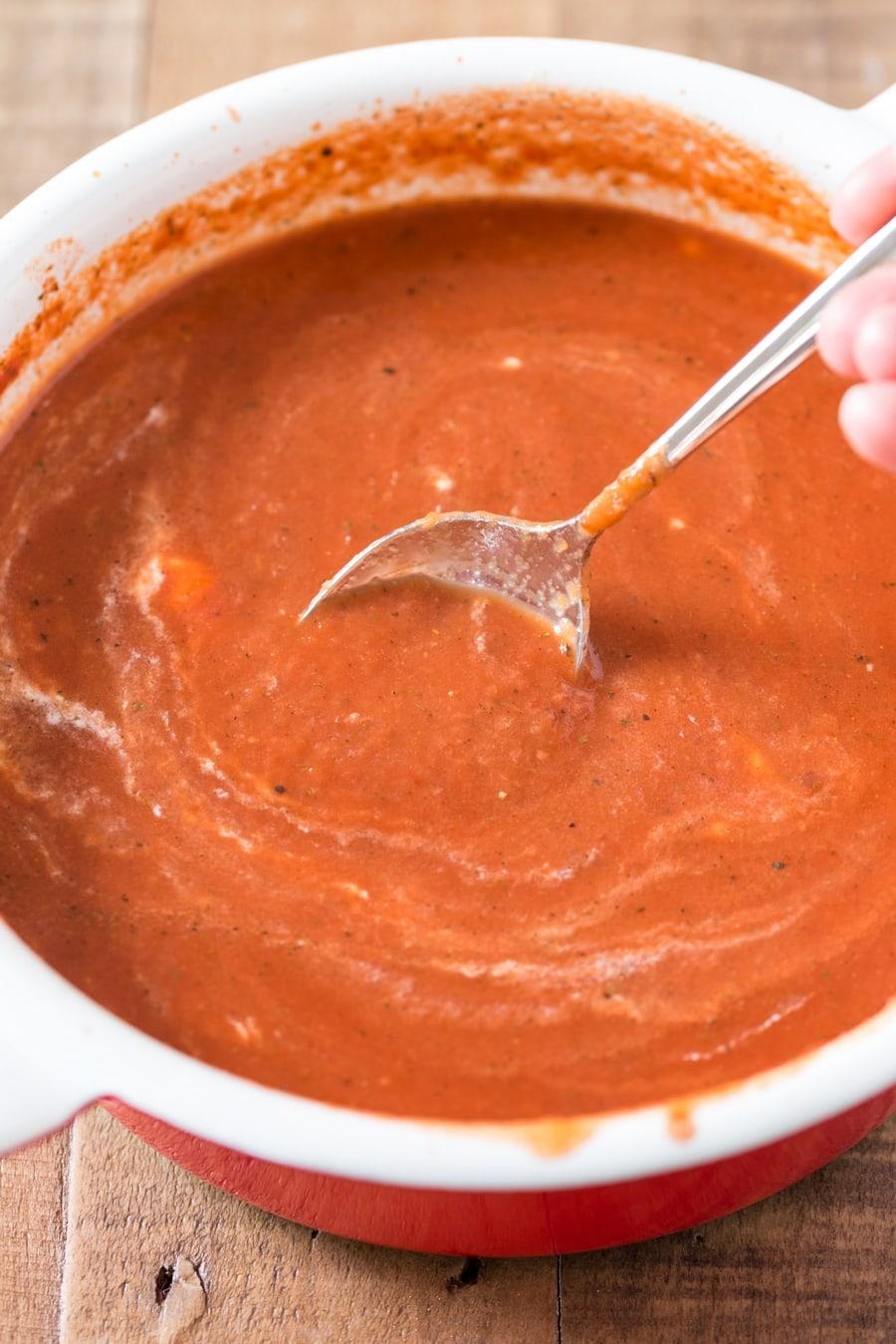 Mixing the cream into Polish tomato soup.