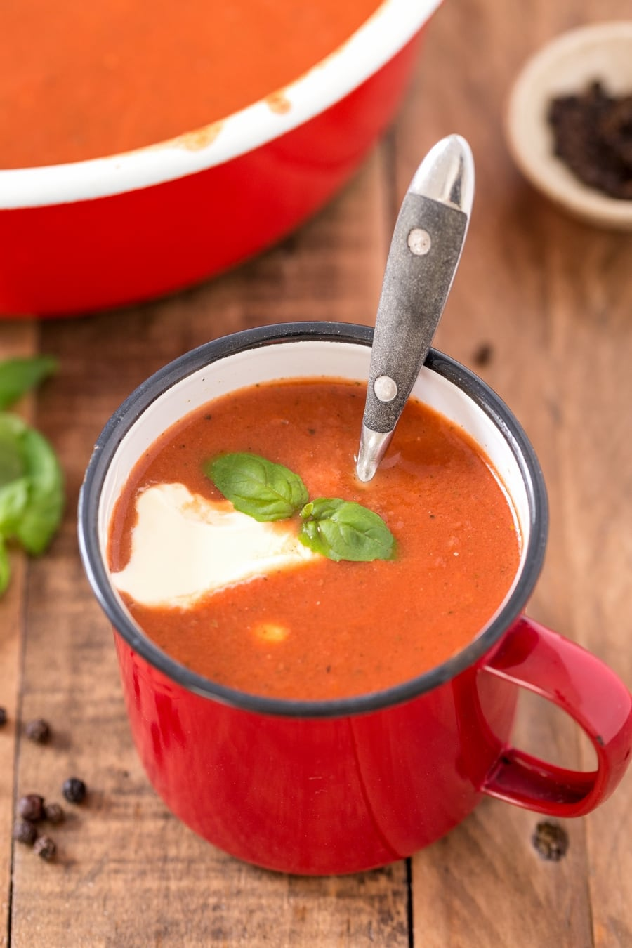 Red metal cup containing pomidorowa soup with a dollop of cream and basil leaves.