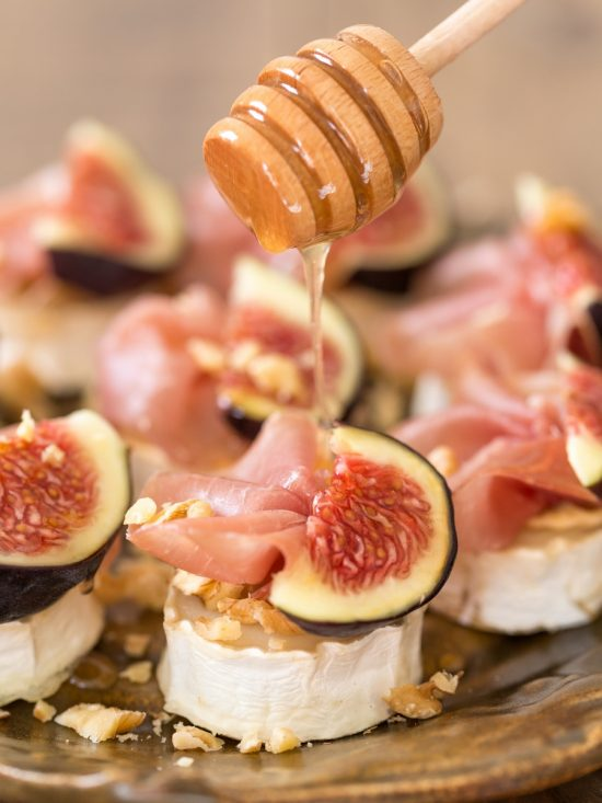 Drizzling honey over baked goat cheese with figs.