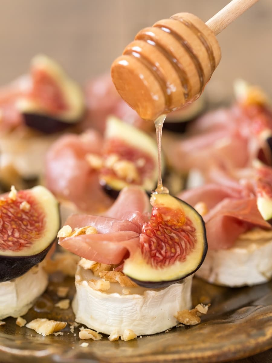 Drizzling honey over baked chevre with figs and prosciutto.