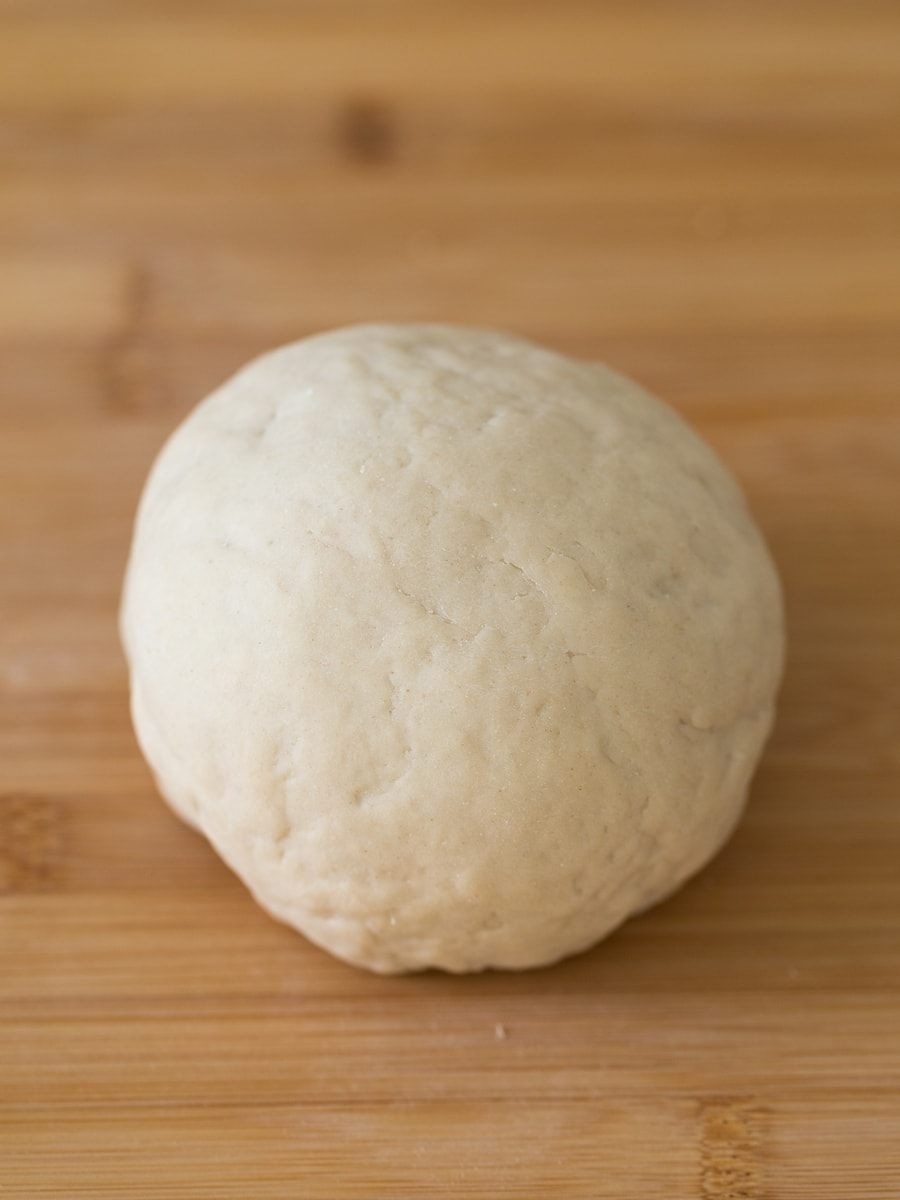 Ball of pierogi dough on wooden surface.