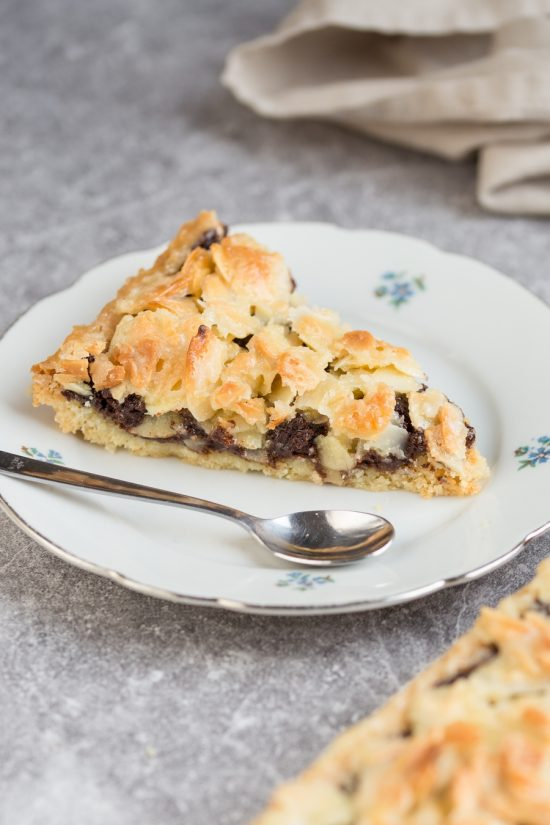 Almond chocolate tart on a gluten-free alond shortcrust. Filled with delicious dark chocolate and topped with glazed almonds, this chocolate almond tart is a delicious dessert option.
