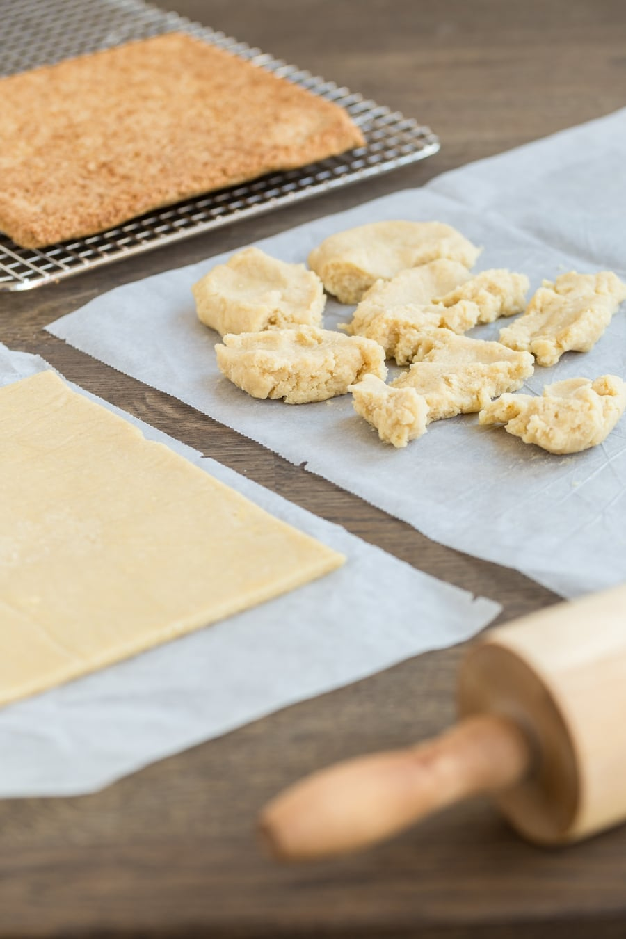 Crumbled pastry dough about to be rolled out between parchment paper sheets.