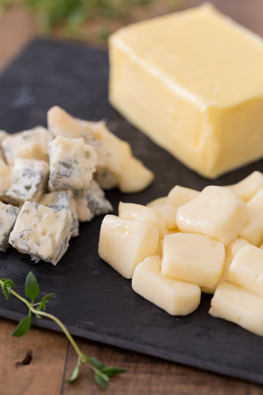 Cubes of taleggio and gorgonzola on a tray, butter in the background.