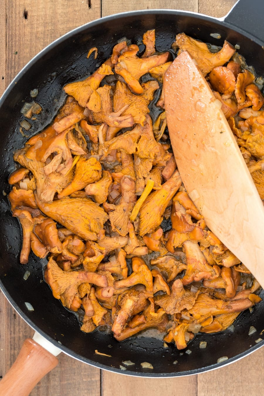 Chanterelles cooked with butter and onion in a skillet.