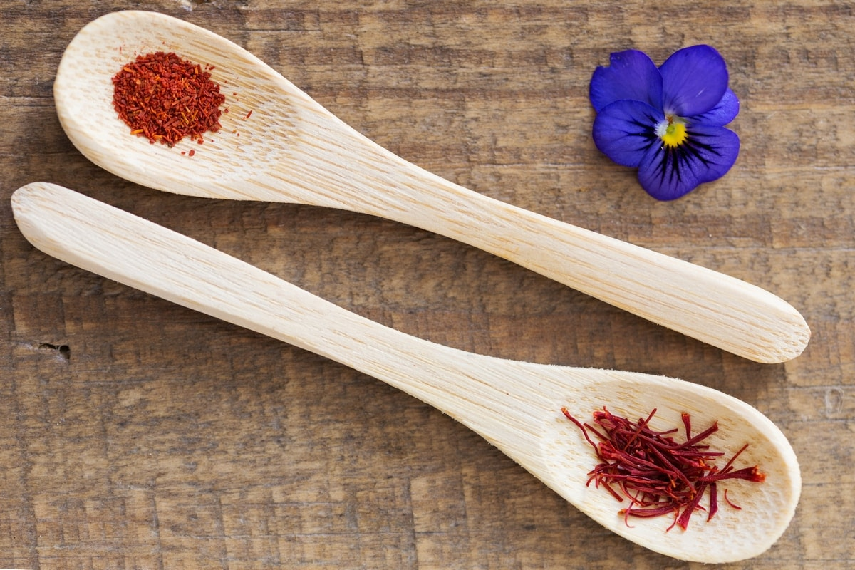 Two small wooden spoons with saffron threads and ground saffron.