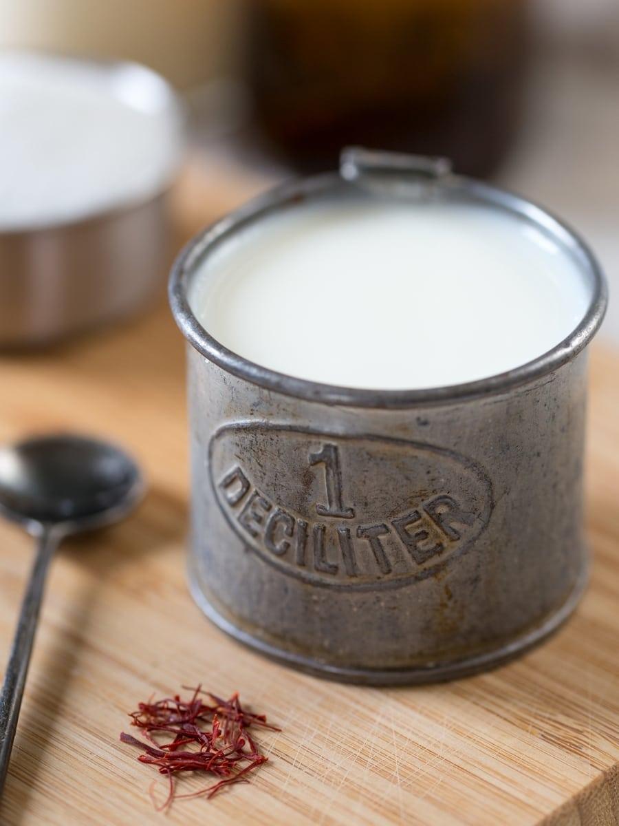 Milk in a tin deciliter container.