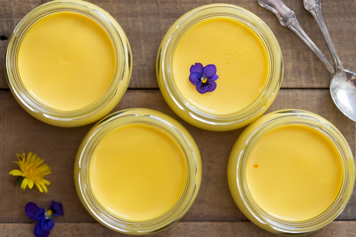 Small glass jars with saffron panna cotta on a wooden table.