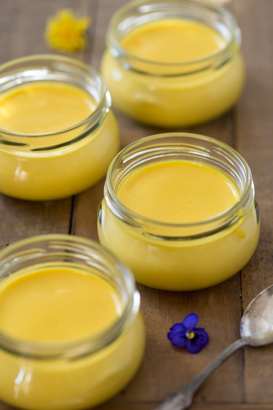 Saffron panna cotta served in small glass containers.