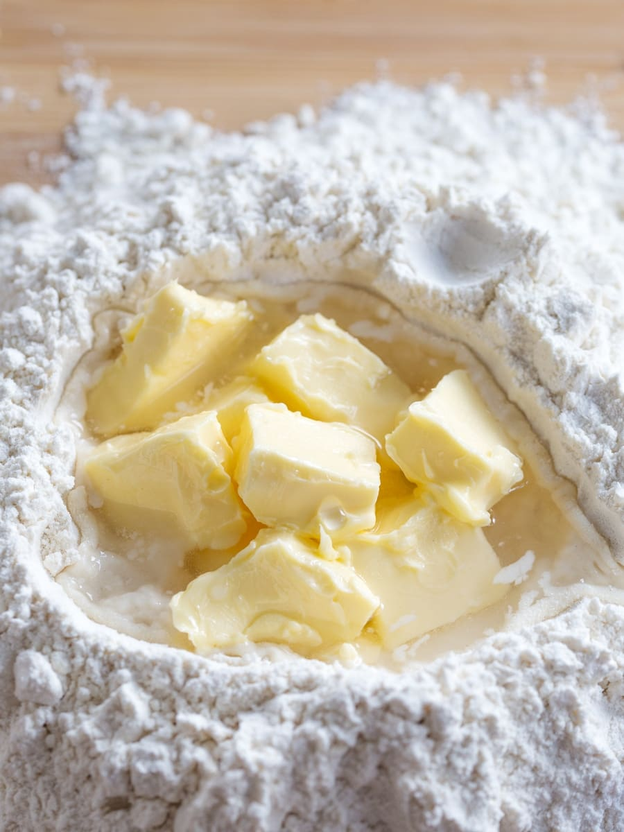 Mound of flour with cubed softened butter and water in the centre.